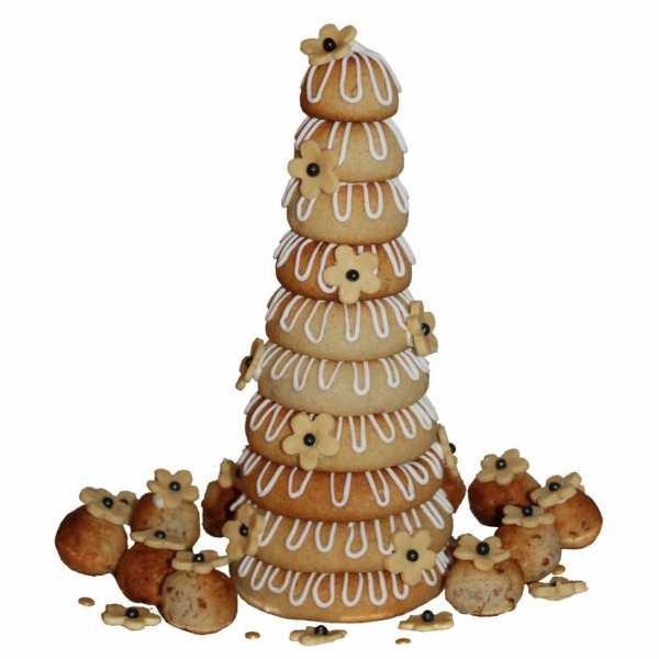 """Pynt kransekagen festligt - brug flag, knallerter, serpentiner eller lignende, eller dekorer med spiseligt pynt f.eks. chokolade eller <a href=""""https://danishthings.com/da/tag/marengs/"""" rel=""""noopener"""" target=""""_blank"""">marengs</a>. Her er kransekagen pyntet med hvide blomster af modeleringschokolade, det samme er de små mandel petite fours"""