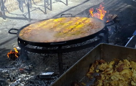 A huge paella pot, at least 4 feet in diameter, over a wood fire