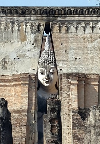 It looks like this Buddha's head is being squeezed but actually it is in a room behind the V shaped Arch.