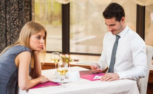 Woman is getting bored on date while her boyfriend is typing sms