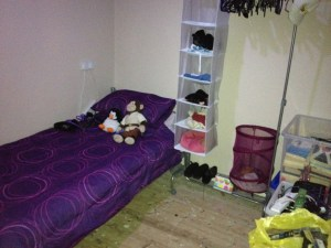 A small bedroom with a single bed in the corner with purple bedding, a clothes rail with hanging shelves, and boxes with items in. There is clear floor space in the middle.