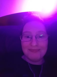 A photo of Danni's face. Their head is resting on a pillow. The entire image is tinted purple from the light in the top right corner.