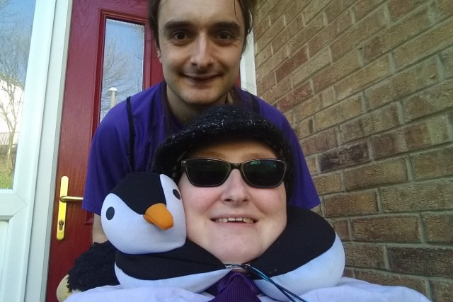 Danni is at the bottom of the image, wearing a shirt and tie, sunglasses and a hat. Above is Johan, who is wearing a purple t-shirt and is leaning down. They both are smiling and are outside.