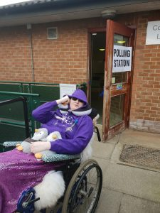 Danni is in the their wheelchair outside a polling station. They are wearing sunglasses, a purple hoodie with the hood up, and a purple sparkly blanket. On their lap are two grey penguins. They have a penguin neck cushion around their neck and their right hand is next to their ear.