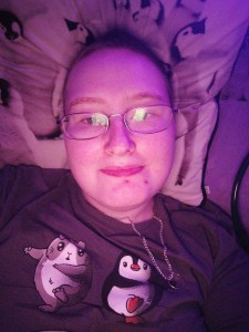 Danni is lying in bed with a small smile. The image is tinted purple from the light.