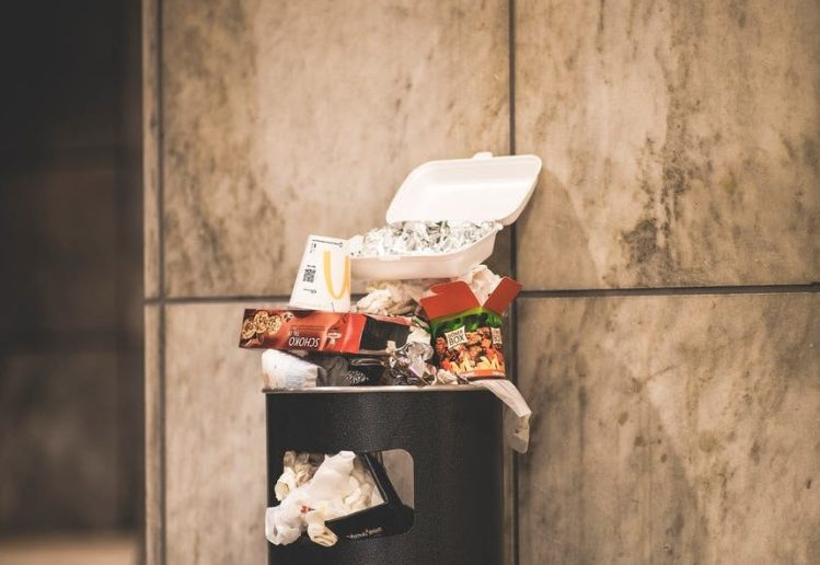 black trash bin with full of trash