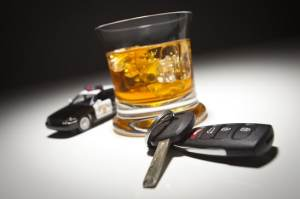 Highway Patrol Police Car Next to Alcoholic Drink and Keys Under Spot Light.