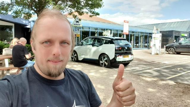 Dan and an eV at a charging point