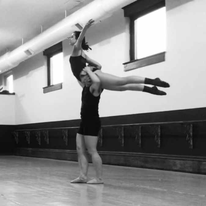 In a ballet studio, the author balances his partner on his shoulder in a modified