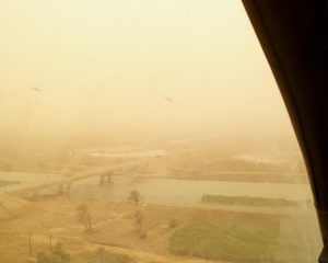 Flying north along Highway 7 into the attack, 26 March 2003.  BT and Spock's aircraft are just visible above the highway and two friendly armored vehicles are underneath them.  Visibility got worse before we called it quits.  pg. 175