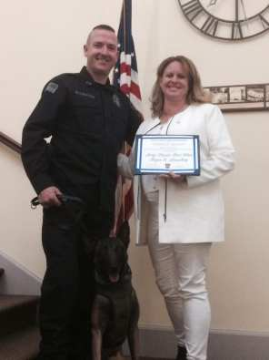 Officer Justin Ellenton & K9 Stryka pose with Karen Lounsbury, who generously donated the funds to secure a protective tactical vest in loving memory of her son, PFC Bryan Lounsbury.