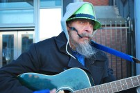"Kieth Sexton of Kent plays his guitar for commuters outside Seattle's King Street Station on Feb. 3. Sexton said he usually plays on Seahawks game days, but will sometimes come by on a weekday to ""keep [people] entertained."" Sexton said that one his favorite memories is having played some Grateful Dead songs while Seahawks' coach Pete Carroll sang along before a game at Century Link Field."