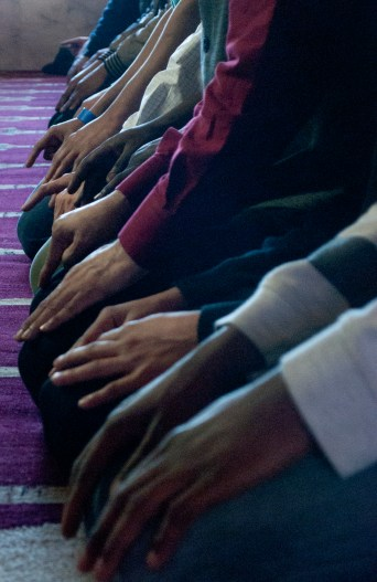 """Members of the Islamic House rest their hands on their knees during a prayer on Friday, Feb. 28, 2014. Muslims' prayers are set to happen a minimum of five times throughout the day and have series of set movements. Completing one set of movements is called a a """"rak'ah."""" During prayer, a Muslim will rest on his or her knees then lean forward to press his or her head onto the floor. This act, which represents humility before God, is done twice in a single rak'ah, with members placing kneeling and placing their hands on their knees in between the two."""