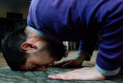 """Mohammad Ahmed performs a """"sujud"""" during his evening prayers on Tuesday, Feb. 25, 2014 in the UW's Husky Union Building. This movement of the prayer represents an act of humility for Muslims before God. The act of bowing is especially significant, Ahmed said, because Arab culture at the time of Islam's founding placed a heavy emphasis on dignity."""