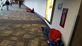 Delta customers sleeping in the concourse hallway.