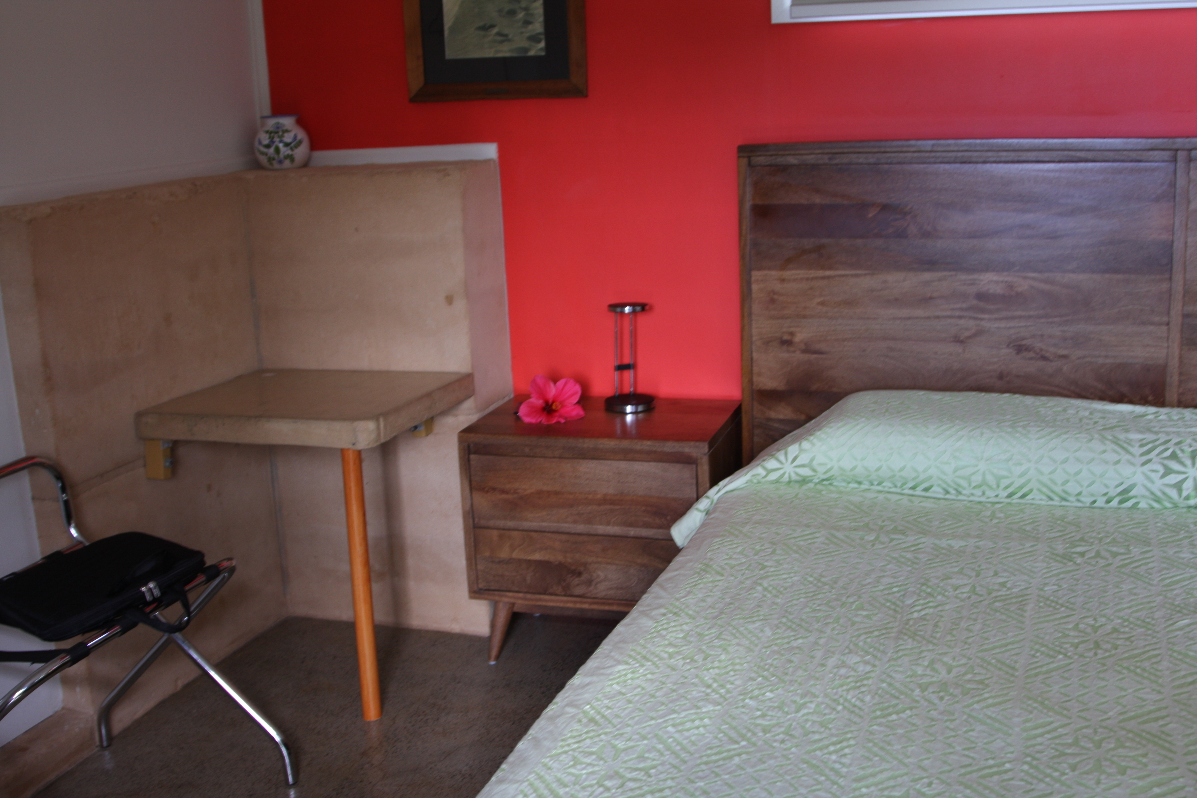 bed, nightstand and one of the three tables at the Wompoo Eco Retreat in the Daintree Rainforest