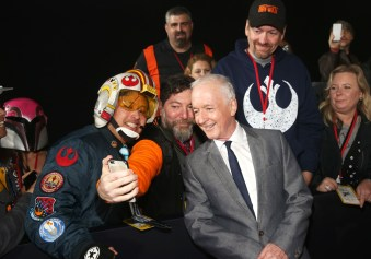 """HOLLYWOOD, CA - DECEMBER 10: Actor Anthony Daniels (R) takes a selfie with fans at The World Premiere of Lucasfilm's highly anticipated, first-ever, standalone Star Wars adventure, """"Rogue One: A Star Wars Story"""" at the Pantages Theatre on December 10, 2016 in Hollywood, California. (Photo by Jesse Grant/Getty Images for Disney) *** Local Caption *** Anthony Daniels"""