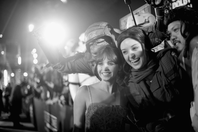 """HOLLYWOOD, CA - DECEMBER 10: (EDITORS NOTE: Image has been shot in black and white. Color version not available.) Actress Felicity Jones poses with a fan at The World Premiere of Lucasfilm's highly anticipated, first-ever, standalone Star Wars adventure, """"Rogue One: A Star Wars Story"""" at the Pantages Theatre on December 10, 2016 in Hollywood, California. (Photo by Charley Gallay/Getty Images for Disney) *** Local Caption *** Felicity Jones"""