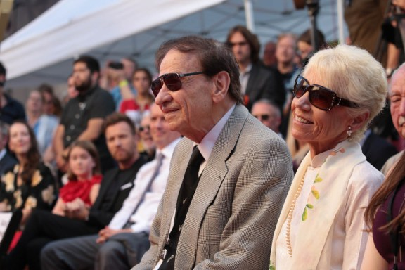 """Richard M. Sherman and Elizabeth Sherman listen on at the dedication and re-naming of the historic Orchestra Stage, now the Sherman Brothers Stage A, on the Disney Burbank lot prior to the world premiere of Disney's """"Christopher Robin"""" at the studio's Main Theater, on July 30, 2018 in Burbank, CA (Photo: Alex J. Berliner/ABImages)"""