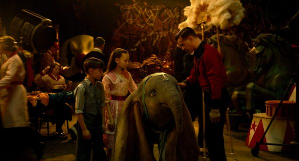 "ON WITH THE SHOW – When a persuasive entrepreneur decides to make Dumbo a star at his larger-than-life entertainment venture, former circus star Holt Farrier (Colin Farrell) and his children Milly (Nico Parker) and Joe (Finley Hobbins) vow to stick with their beloved flying elephant the whole way. Directed by Tim Burton, Disney's all-new, live-action, big-screen adventure ""Dumbo"" flies into theaters on March 29, 2019. ©2018 Disney Enterprises, Inc. All Rights Reserved."