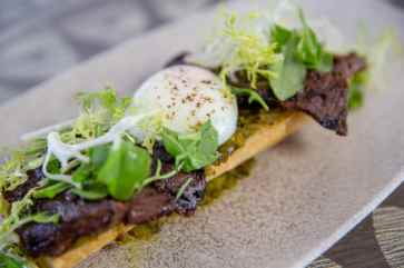 Grilled Skirt Steak served over a grilled baguette with pepper relish and topped with egg is offered at Three Bridges Bar & Grill in Disney's Coronado Springs Resort at Walt Disney World Resort in Lake Buena Vista, Florida. (Steven Diaz, photographer)