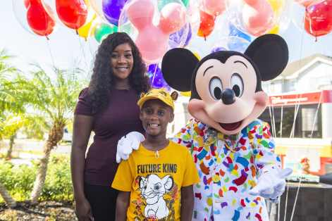 Mickey Mouse makes a surprise appearance at seven-year-old Jermaine Bell's birthday party Sept. 8, 2019, in Kissimmee, Fla. Mickey and Walt Disney World cast members were there to honor Jermaine who used money he'd saved for a Walt Disney World vacation to feed people fleeing Hurricane Dorian. Adding to a day filled with surprises, Jermaine learned that he and his family will be guests of Disney for a VIP getaway to the vacation kingdom later this month. Pictured, from left to right, are Jermaine's mother, Laura Creech; Jermaine Bell; and Mickey Mouse. (Disney)