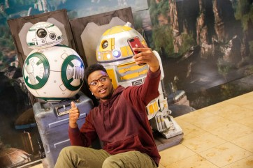 A guest at Orlando International Airport stops to take a selfie with droids from Star Wars: Galaxy's Edge outside the airport's Magic of Disney store in the Main Terminal, Nov. 16, 2019, in Orlando, Fla. The droids were brought to the airport to help airport guests feel some of the fun and excitement of the new land at Disney's Hollywood Studios at Walt Disney World Resort. (Steven Diaz, photographer)