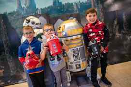 Three children pose for a photo with droids from Star Wars: Galaxy's Edge outside the Magic of Disney store at Orlando International Airport in Orlando, Fla., Nov. 16, 2019. Disney brought the droids to the airport so guests can feel the fun and excitement of the new land at Disney's Hollywood Studios at Walt Disney World Resort. (Steven Diaz, photographer)