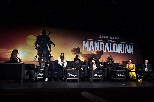 "HOLLYWOOD, CALIFORNIA - NOVEMBER 13: (L-R) Moderator Ash Crossan, Executive Producer Jon Favreau, Composer Ludwig Göransson, Executive Producer/Director Dave Filoni, Director Deborah Chow, Pedro Pascal, Rick Famuyiwa, Carl Weathers, Director Bryce Dallas Howard, Gina Carano and Werner Herzog speak onstage at the premiere of Lucasfilm's first-ever, live-action series, ""The Mandalorian,"" at the El Capitan Theatre in Hollywood, Calif. on November 13, 2019. ""The Mandalorian"" streams exclusively on Disney+. (Photo by Alberto E. Rodriguez/Getty Images for Disney)"