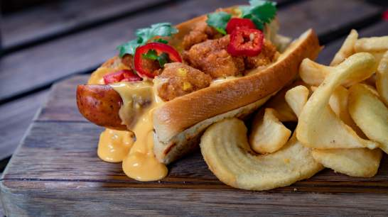 "The Cheesy ""Corn"" Dog is part of the limited-time Holiday foods at The Disneyland Resort. Available November 8 - January 6, this dish is a jalapeno-cheddar sausage, topped with tangy corn-cheese sauce, chili-lime-dusted corn fritters and cilantro on a toasted potato bun. This item can be be purchased at Award Weiners in Disney California Adventure Park. (Disneyland Resort)"