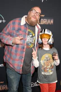 "HOLLYWOOD, CALIFORNIA - NOVEMBER 13: (L-R) Brian Posehn and son arrive at the premiere of Lucasfilm's first-ever, live-action series, ""The Mandalorian,"" at the El Capitan Theatre in Hollywood, Calif. on November 13, 2019. ""The Mandalorian"" streams exclusively on Disney+. (Photo by Jesse Grant/Getty Images for Disney)"
