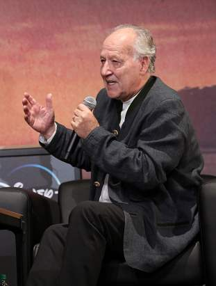 "HOLLYWOOD, CALIFORNIA - NOVEMBER 13: Werner Herzog speaks onstage at the premiere of Lucasfilm's first-ever, live-action series, ""The Mandalorian,"" at the El Capitan Theatre in Hollywood, Calif. on November 13, 2019. ""The Mandalorian"" streams exclusively on Disney+. (Photo by Jesse Grant/Getty Images for Disney)"