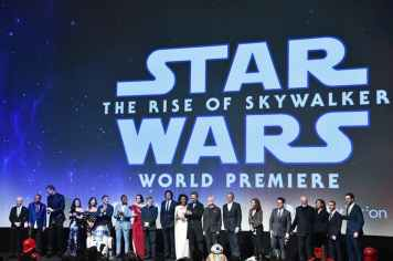 "HOLLYWOOD, CALIFORNIA - DECEMBER 16: (L-R) Anthony Daniels, Billy Dee Williams, Joonas Suotamo, Kelly Marie Tran, Keri Russell, Oscar Isaac, John Boyega, Daisy Ridley, Mark Hamill, Adam Driver, Naomi Ackie, Richard E. Grant, Ian McDiarmid, The Walt Disney Company Chairman and CEO Bob Iger, Producer and President of Lucasfilm Kathleen Kennedy, Director, Writer and Producer J.J. Abrams, composer John Williams, producer Michelle Rejwan, Writer Chris Terrio and executive producer Callum Greene speak onstage during the World Premiere of ""Star Wars: The Rise of Skywalker"", the highly anticipated conclusion of the Skywalker saga on December 16, 2019 in Hollywood, California. (Photo by Alberto E. Rodriguez/Getty Images for Disney)"
