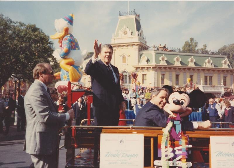 Ronald Reagan, Michael Eisner and Mickey Mouse travel down the parade route.