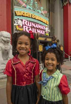 Two young guests stop for a photo in front of the marquee for Mickey & Minnie's Runaway Railway on opening day of the new family-friendly attraction, March 4, 2020, in Disney's Hollywood Studios at Walt Disney World Resort in Lake Buena Vista, Fla. (Kent Phillips, photographer)