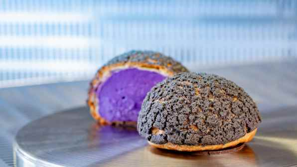 Terran Treats in Avengers Campus inside Disney California Adventure Park in Anaheim, California, features a weird and wonderful menu of intergalactic eats. Here, guests can indulge in this Cosmic Cream Orb, a crispy cream puff with whipped raspberry cheesecake mousse. Avengers Campus opens July 18, 2020. (David Nguyen/Disneyland Resort)