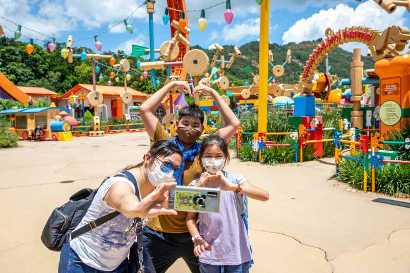 Guests take selfies on the reopening day of Hong Kong Disneyland.