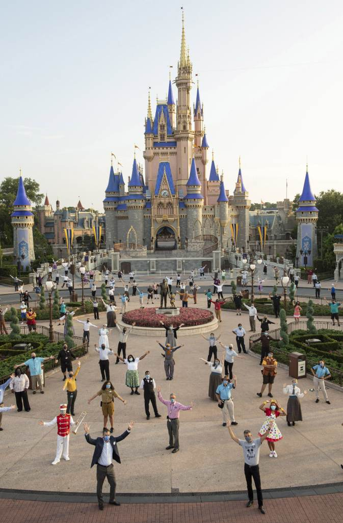 Josh D'Amaro, chairman, Disney Parks, Experiences and Products (center front right) and Jeff Vahle, president, Walt Disney World Resort (center front left), pose with Disney cast members for a photo in front of Cinderella Castle, July 11, 2020, prior to the phased reopening of Magic Kingdom Park at Walt Disney World Resort in Lake Buena Vista, Fla. (David Roark, photographer)