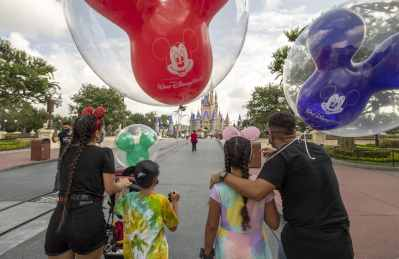 Guests walk down Main Street, U.S.A. at Magic Kingdom Park, July 11, 2020, at Walt Disney World Resort in Lake Buena Vista, Fla., on the first day of the theme park's phased reopening. (Kent Phillips, Photographer)