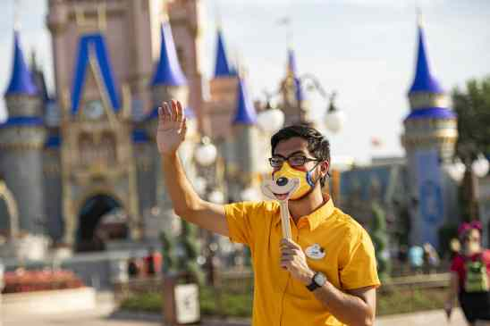 A Disney cast member welcomes guests to Magic Kingdom Park, July 11, 2020, at Walt Disney World Resort in Lake Buena Vista, Fla., on the first day of the theme park's phased reopening. (Matt Stroshane, photographer)