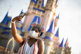 A guest stops to take a selfie at Magic Kingdom Park, July 11, 2020, at Walt Disney World Resort in Lake Buena Vista, Fla., on the first day of the theme park's phased reopening. (Olga Thompson, photographer)