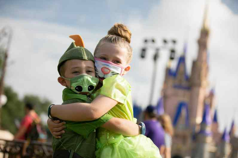 Two young guests stop to take a photo at Magic Kingdom Park, July 11, 2020, at Walt Disney World Resort in Lake Buena Vista, Fla., on the first day of the theme park's phased reopening. (Olga Thompson, photographer)