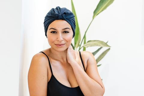 Woman wearing a navy blue silk headwrap and smiling. She is standing in front of a green plant.