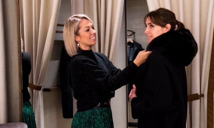 Stylist helping a woman try on a coat