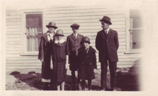 the Holm family in front of the farmhouse