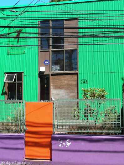 Colourful renovation of an old house, clad in corrugated iron.