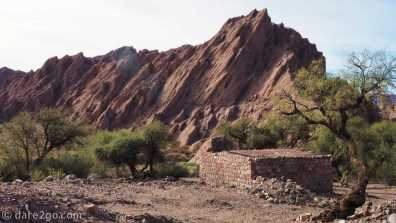 Paso San Francisco, Argentina: a house built from multi-coloured rocks in front of another amazing rock structure
