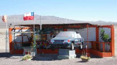 East of Calama, Chile: huge roadside shrine, complete with a car, bench seat, and lots of green plants, in the middle of a desert.