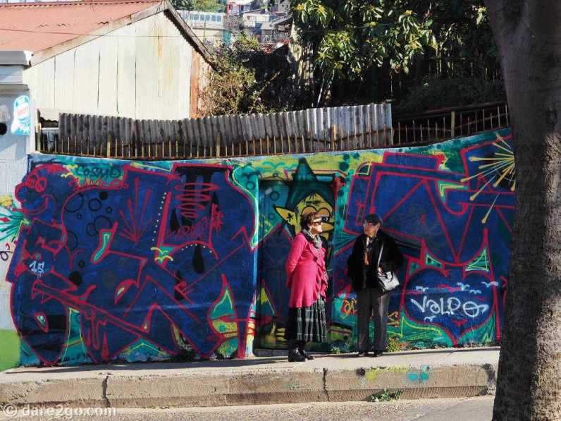 Valparaiso StreetArt scene: women (colour matched) in front of graffiti, waiting for the bus