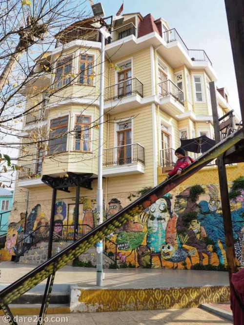 Valparaiso StreetArt: at the top of Cerro Constitucion, where the funicular ends, is a small plaza surrounded with street art. This old dame of a house has its retaining wall painted.